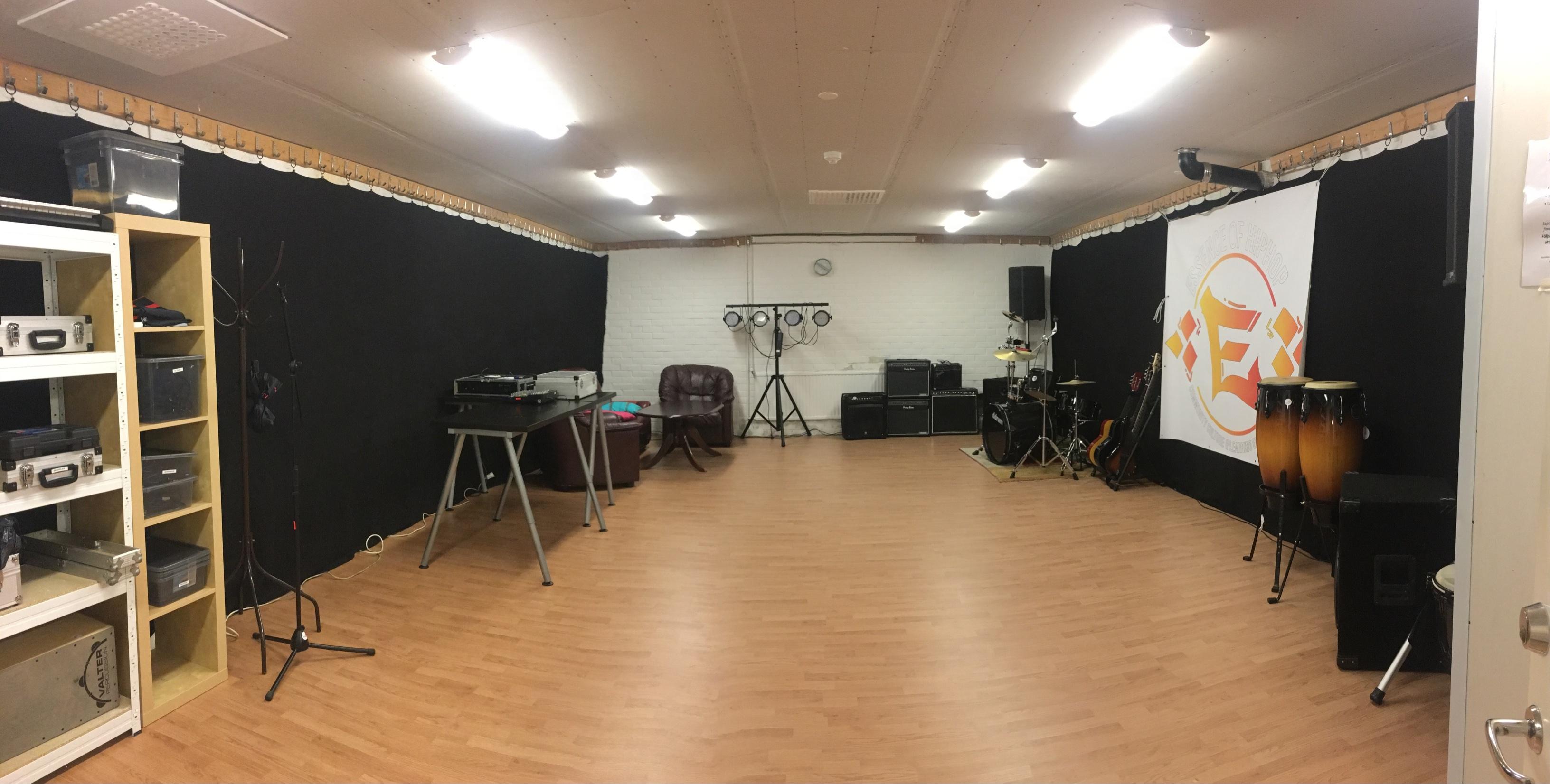 Replokalsbild. Brunt golv, svarta draperier längst väggarna, hyllor på vänster sida samt musikutrustning rakt fram.