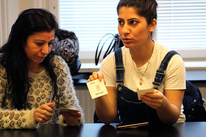 Hanan och Samira berättar för de övriga i gruppen vad de har för matvaror på sina kort och vad de kostar.