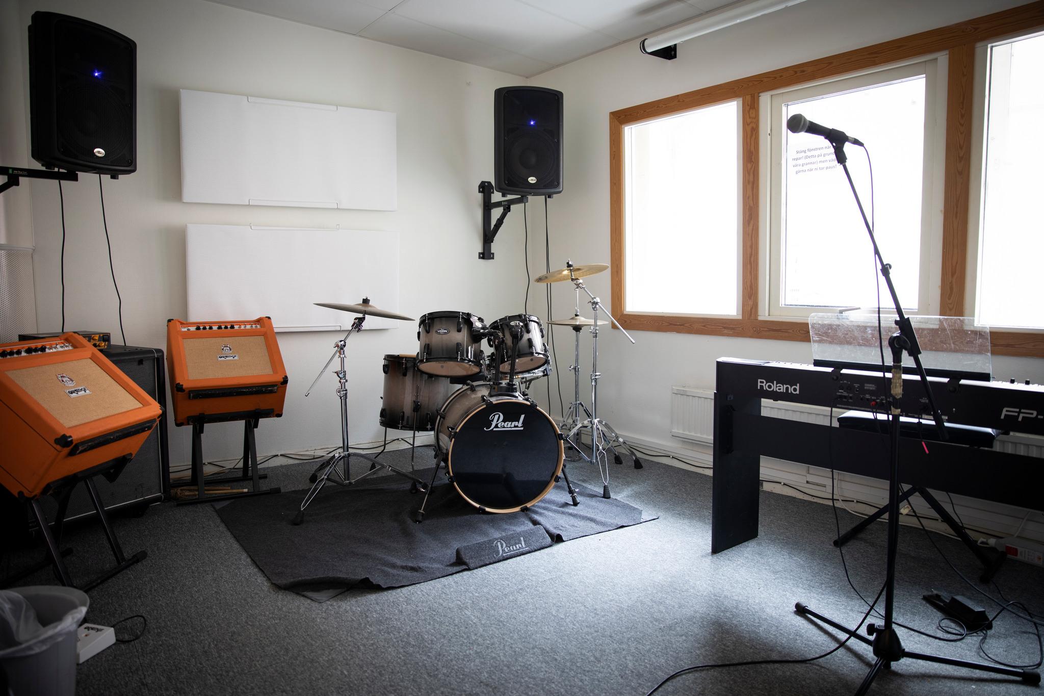 Replokal med elpiano, trummor, mikrofoner och PA